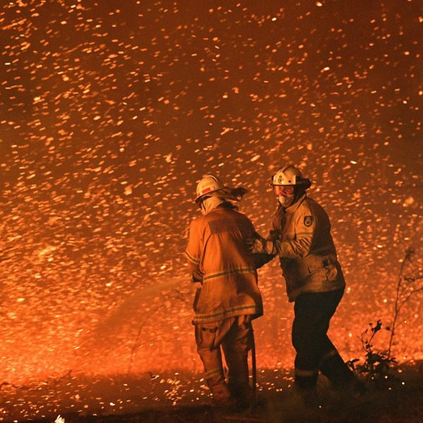 This picture taken on December 31, 2019 shows firefighters struggling against the strong wind in an effort to secure nearby houses from bushfires near the town of Nowra in the Australian state of New South Wales. (Credit: Saeed Khan/AFP via Getty Images)