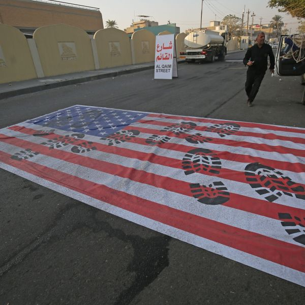 A mock US flag is laid on the ground for cars to drive on in the Iraqi capital Baghdad on January 3, 2020, following news of the killing of Iranian Revolutionary Guards top commander Qasem Soleimani in a US strike on his convoy at Baghdad international airport. (Credit: AHMAD AL-RUBAYE/AFP via Getty Images)