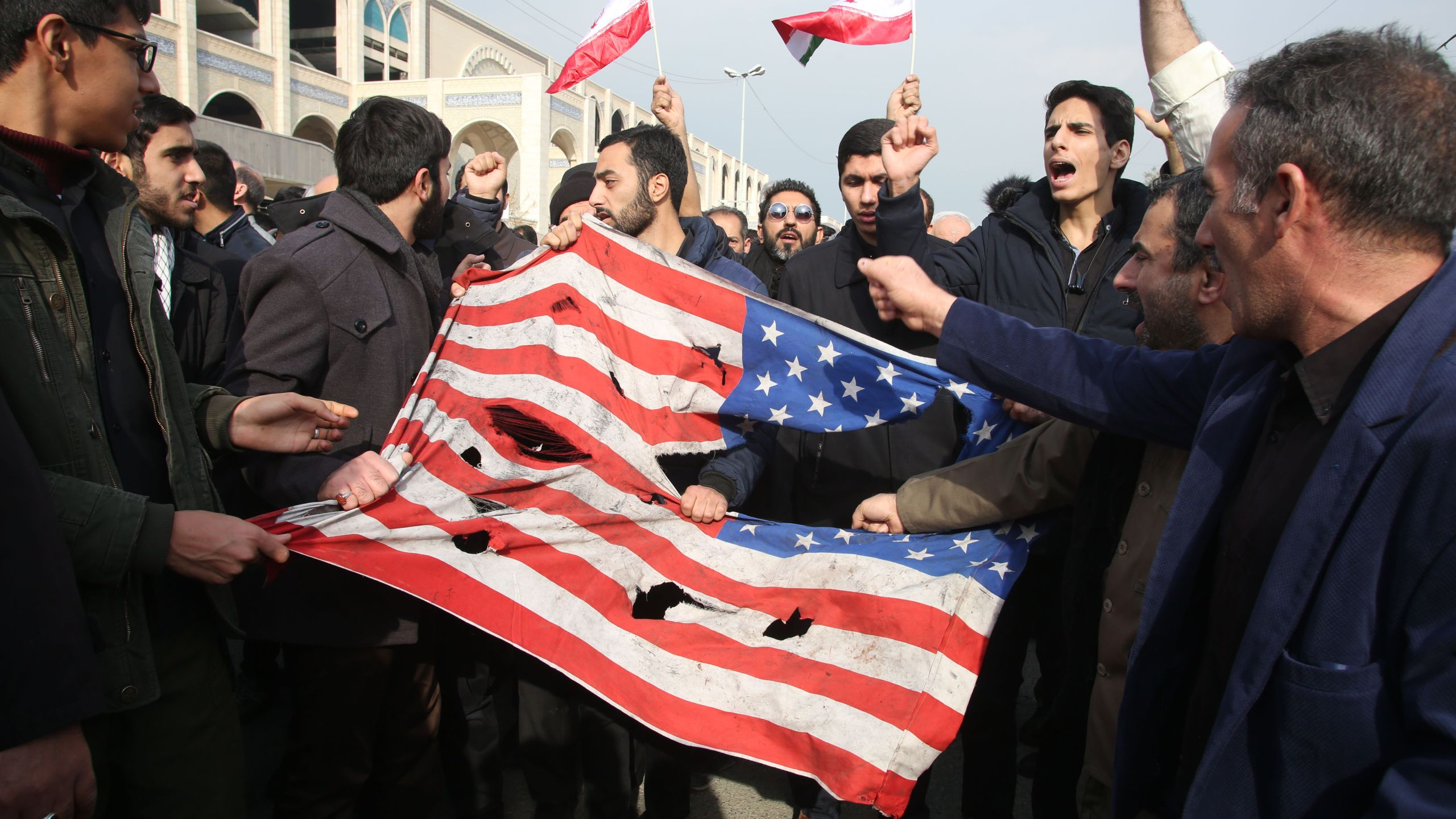 Iranians tear up a U.S. flag during a demonstration in Tehran on Jan. 3, 2020, following the killing of Iranian Revolutionary Guards Major General Qasem Soleimani in a U.S. strike on his convoy at Baghdad international airport. (Credit: Atta Kenare/AFP via Getty Images)