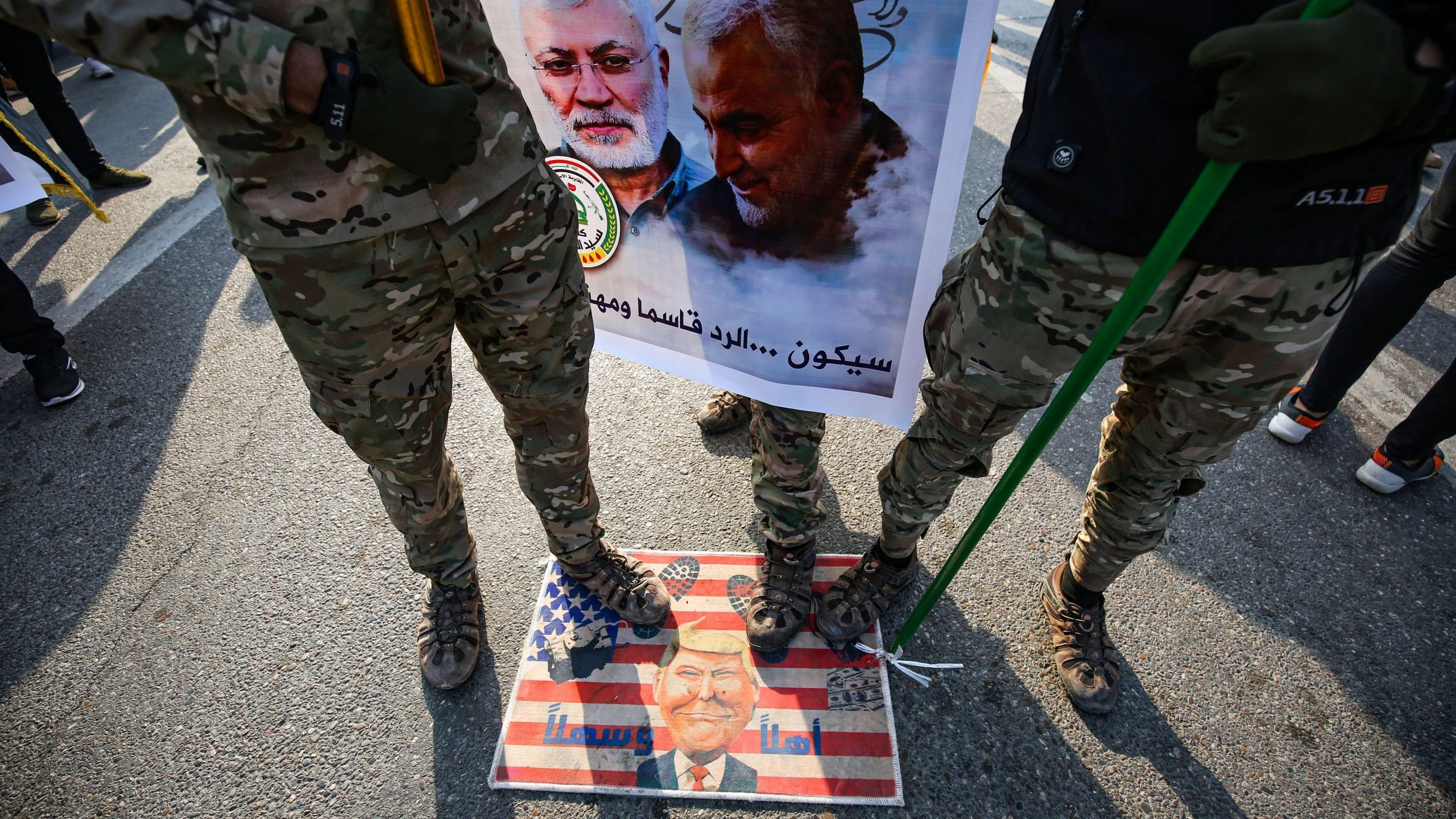 Members of the Hashed al-Shaabi paramilitary force step on a makeshift U.S. flag bearing a caricature of Donald Trump during the funeral procession of Abu Mahdi al-Muhandis, Qassem Soleimani and eight others in the capital Baghdad's district of al-Jadriya, near the high-security Green Zone, on Jan. 4, 2020. (Credit: AHMAD AL-RUBAYE/AFP via Getty Images)