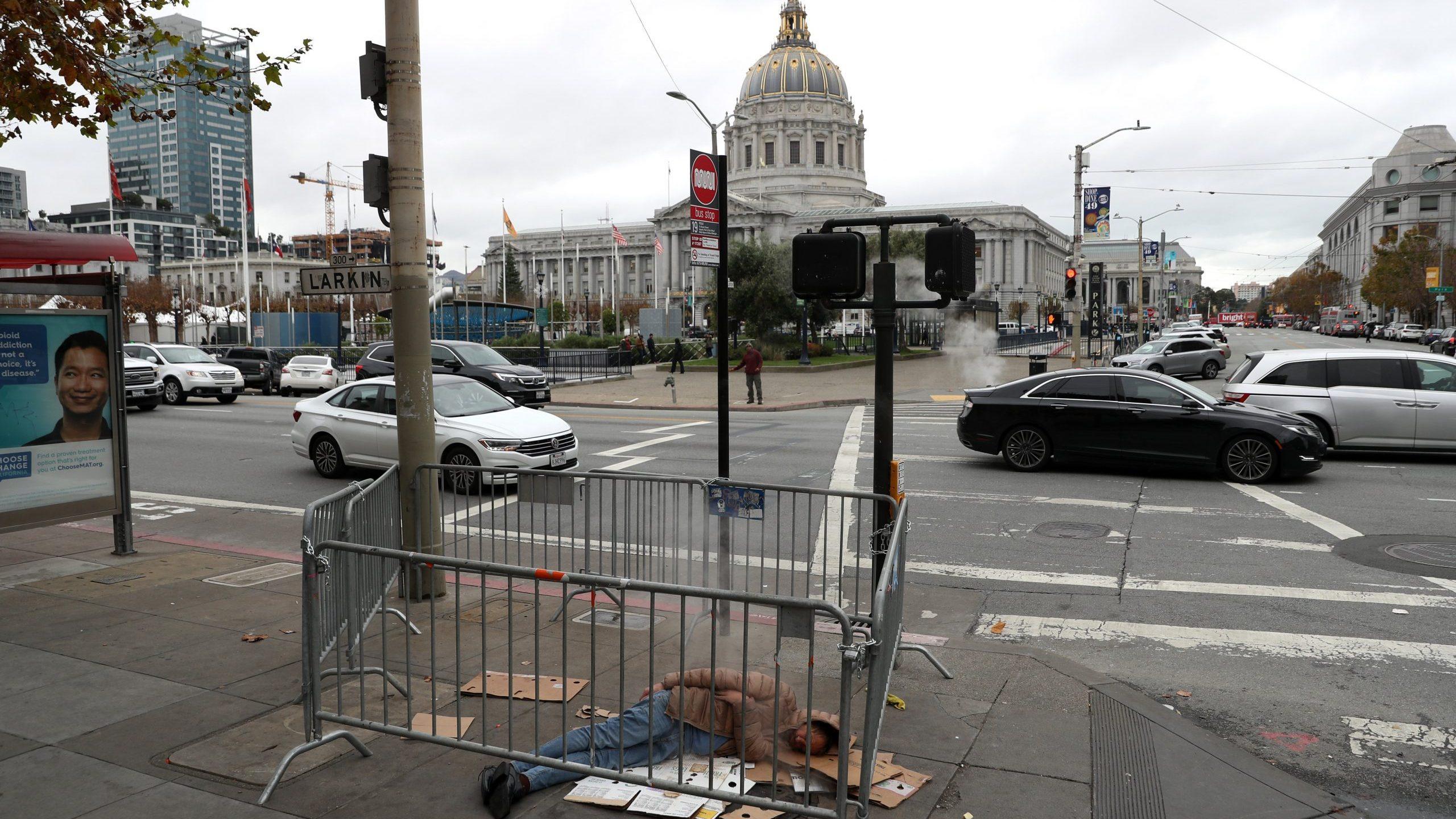 A homeless man sleeps on the sidewalk near San Francisco City Hall on Dec. 5, 2019, in San Francisco, California. (Credit: Justin Sullivan/Getty Images)