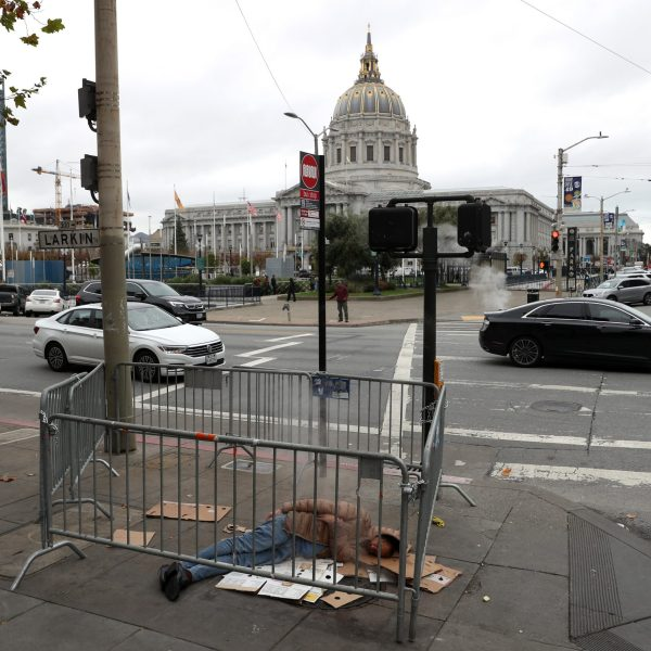 A homeless man sleeps on the sidewalk near San Francisco City Hall on Dec. 5, 2019, in San Francisco, California. (Credit: Justin Sullivan/Getty Images)