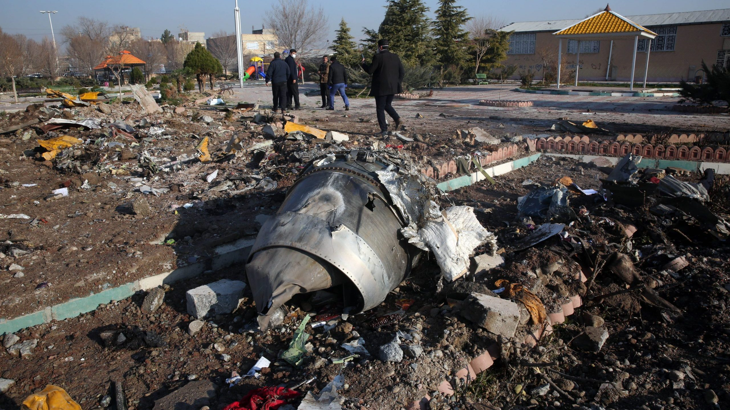 Rescue teams work amidst debris after a Ukrainian plane carrying 176 passengers crashed near Imam Khomeini airport in the Iranian capital Tehran early in the morning on Jan. 8, 2020, killing everyone on board. (Credit: AFP via Getty Images)