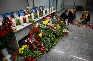 Flight staffers place candles in front of a memorial for the victims of the Ukraine International Airlines Boeing 737-800 crash in the Iranian capital Tehran, at the Boryspil airport outside Kiev on January 8, 2020. (Credit: SERGEI SUPINSKY/AFP via Getty Images)