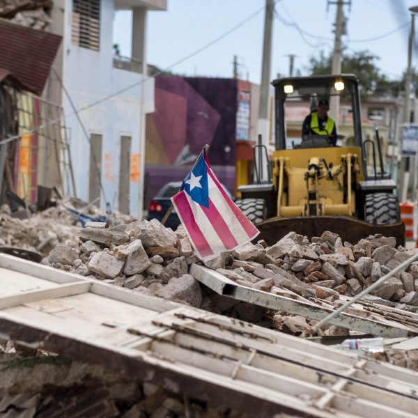 A Puerto Rican flag waves on top of a pile of rubble as debris is removed from a main road in Guanica, Puerto Rico on Jan. 8, 2020. (Credit: RICARDO ARDUENGO/AFP via Getty Images)