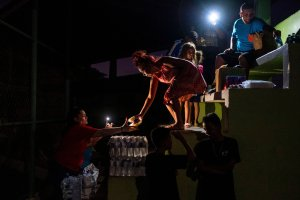 People share food and water on a baseball field where they are sleeping outdoors in Guanica, Puerto Rico, on Jan. 9, 2020, after a powerful earthquake hit the island. (Credit: Ricardo Arduengo / AFP / Getty Images)