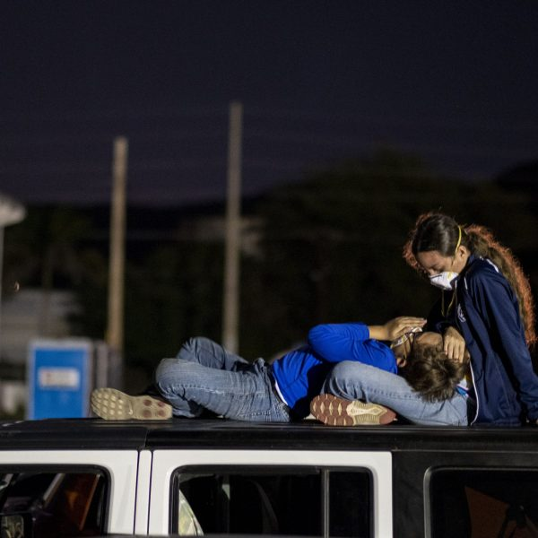 Rachael Peet, 17, and her younger brother Phillip lay on top of a Jeep in a parking lot in Guanica, Puerto Rico, on Jan. 9, 2020, after a powerful earthquake hit the island. (Credit: Ricardo Arduengo / AFP / Getty Images)