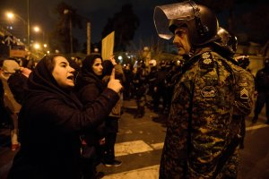 A woman attending a candlelight vigil, in memory of the victims of Ukraine International Airlines Boeing 737, talks to a policeman following the gathering in front of the Amirkabir University in the Iranian capital Tehran on Jan. 11, 2020. (Credit: MONA HOOBEHFEKR/ISNA/AFP via Getty Images)