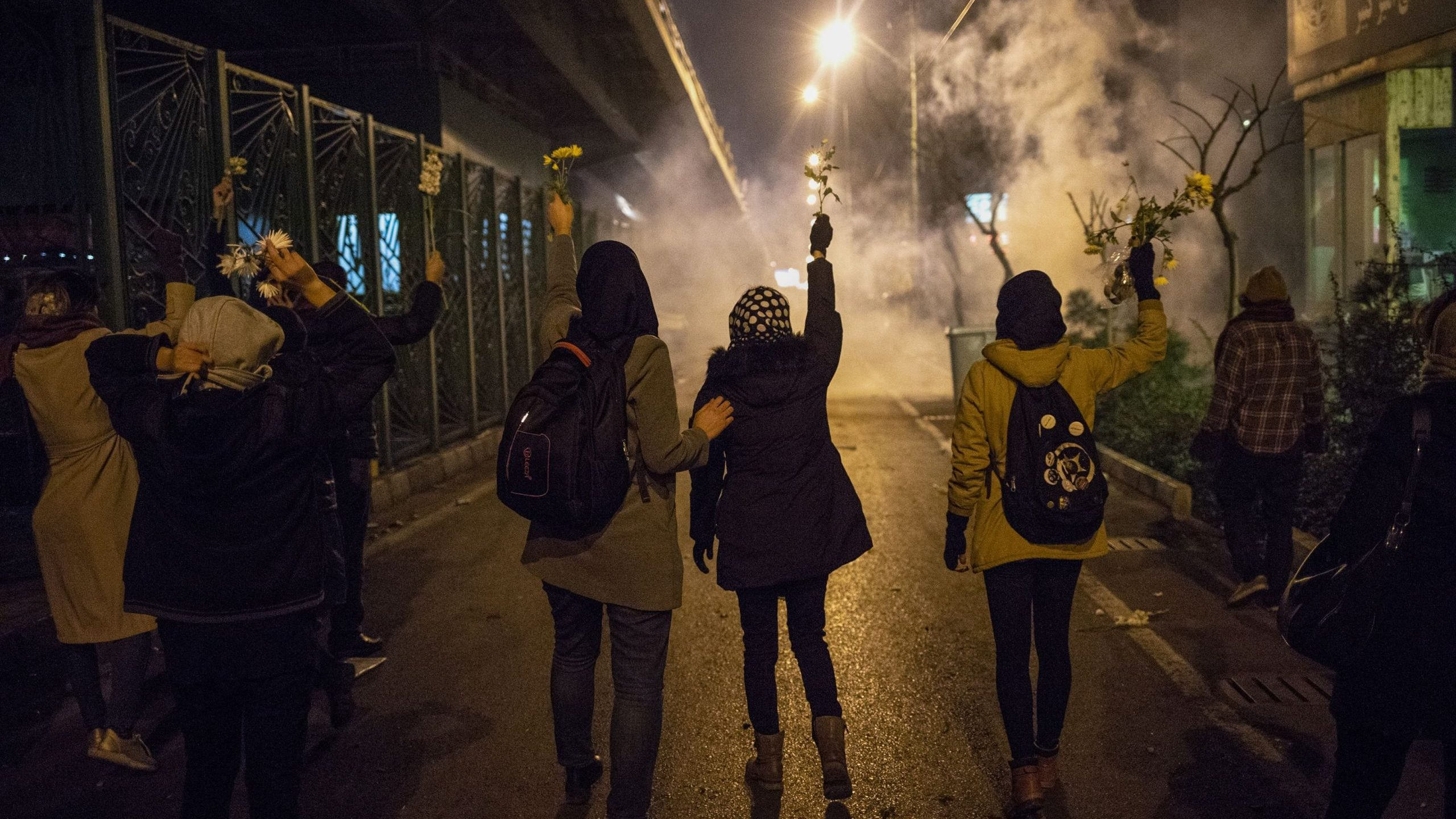 Iranian protesters hold flowers as riot police fire tear gas during a demonstration in front of Tehran's Amir Kabir University on January 11, 2020. (Credit: STR/AFP via Getty Images)