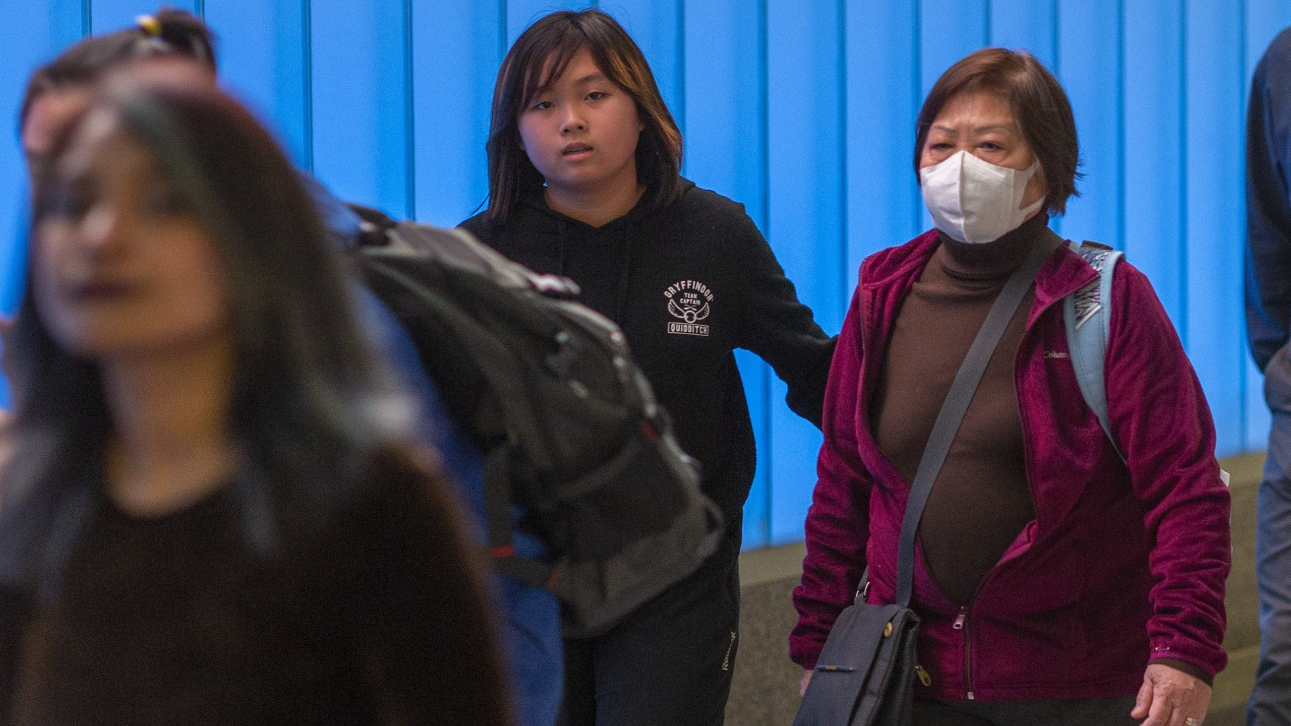 A woman arriving on an international flight to Los Angeles International Airport wears a mask on the first day of health screenings for coronavirus of travelers from Wuhan, China on Jan. 18, 2020. (Credit: David McNew/Getty Images)