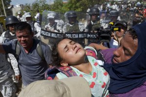 A Central American migrant traveling with a caravan carries a girl after Mexican security forces prevent them from illegally crossing into Ciudad Hidalgo, Mexico, from Guatemala on Jan. 20, 2020. (Credit: Isaac Guzman / AFP / Getty Images)