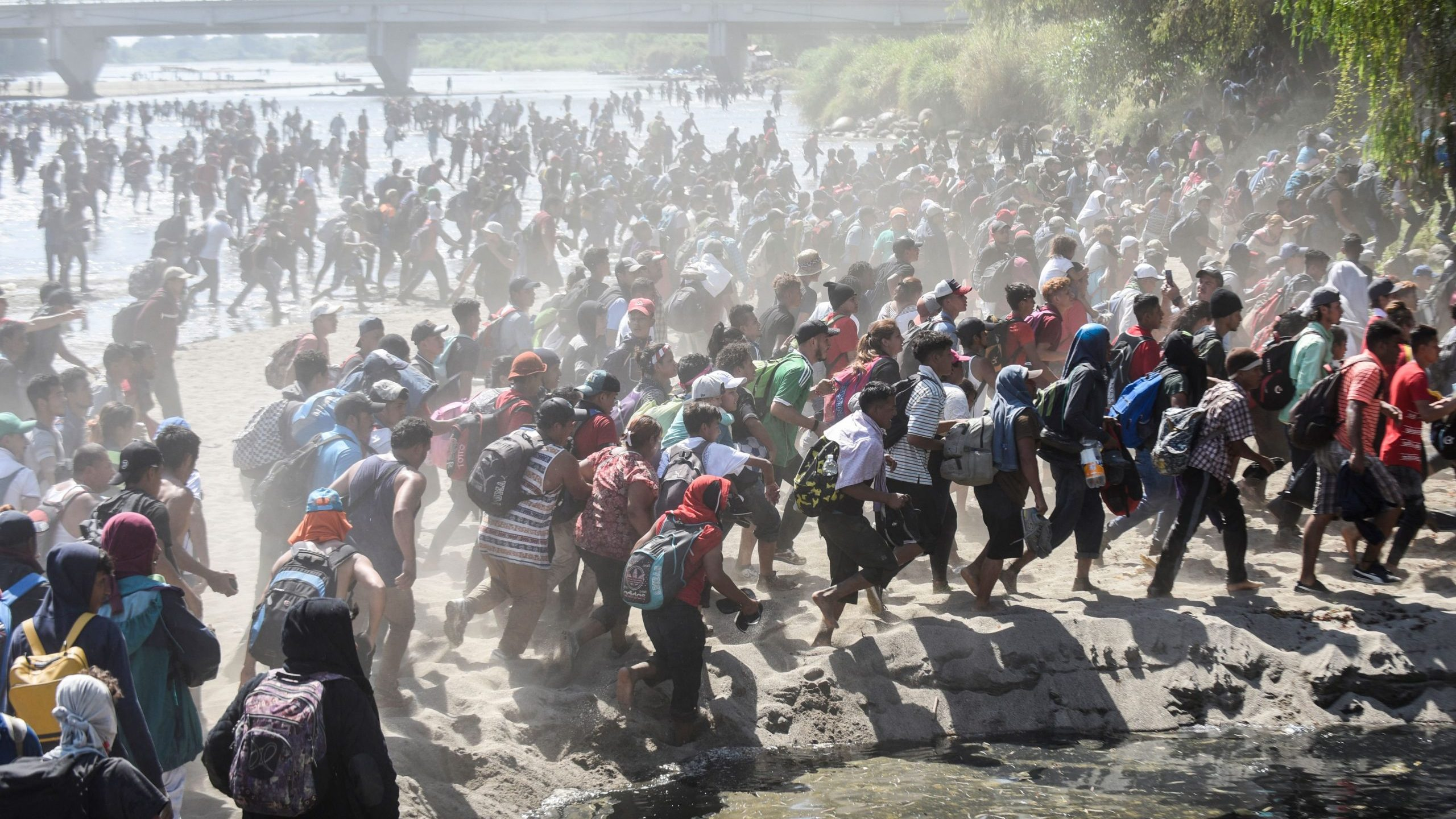 Central American migrants traveling in caravan cross the Suchiate River, the natural border between Guatemala and Mexico, near Ciudad Hidalgo on Jan. 20, 2020. (Credit: Johan Ordonez / AFP / Getty Images)