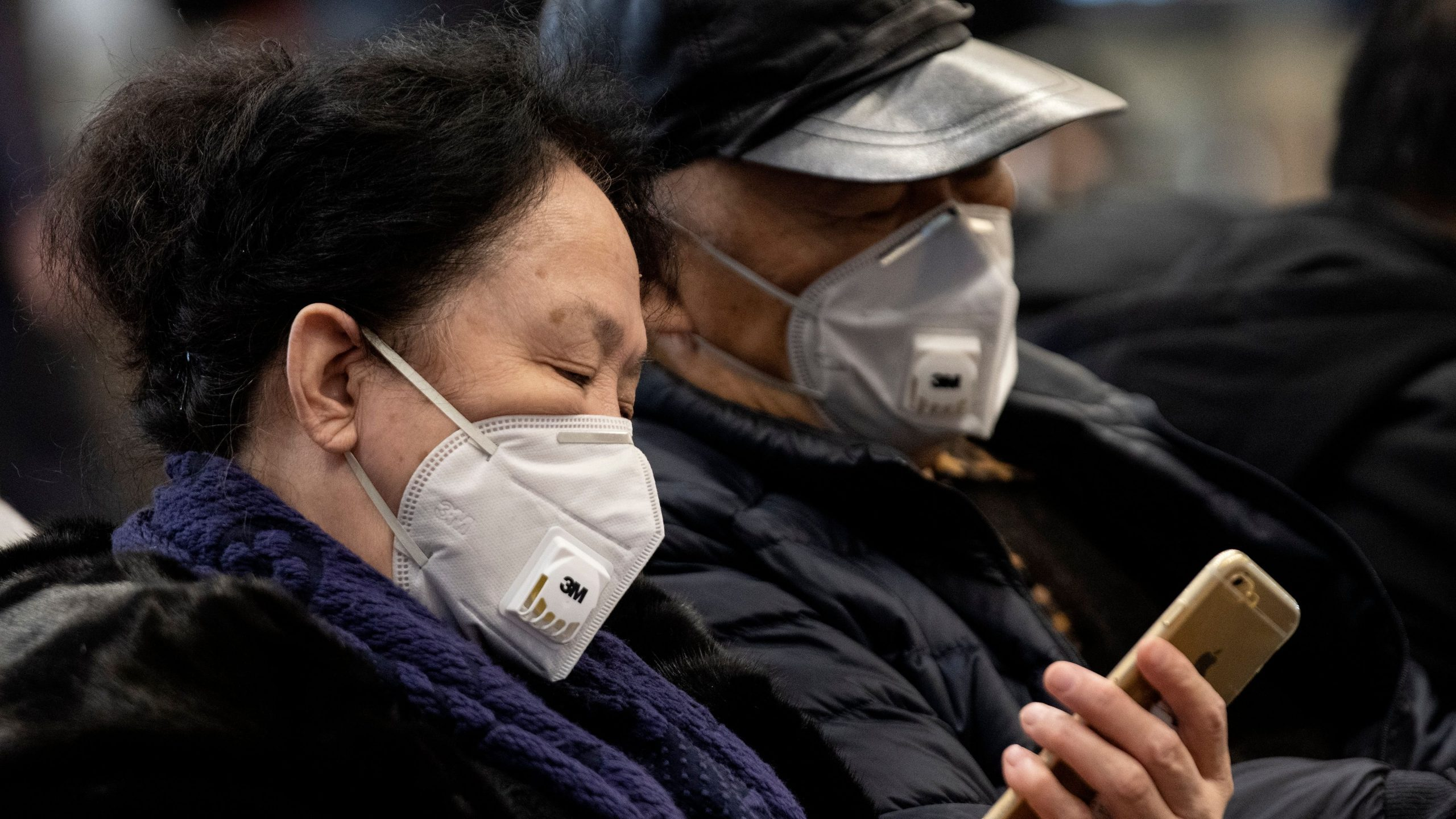 Travelers wearing protective rest on a bench after arriving at the Beijing Capital Airport in Beijing on Jan. 21, 2020. (Credit: NOEL CELIS/AFP via Getty Images)