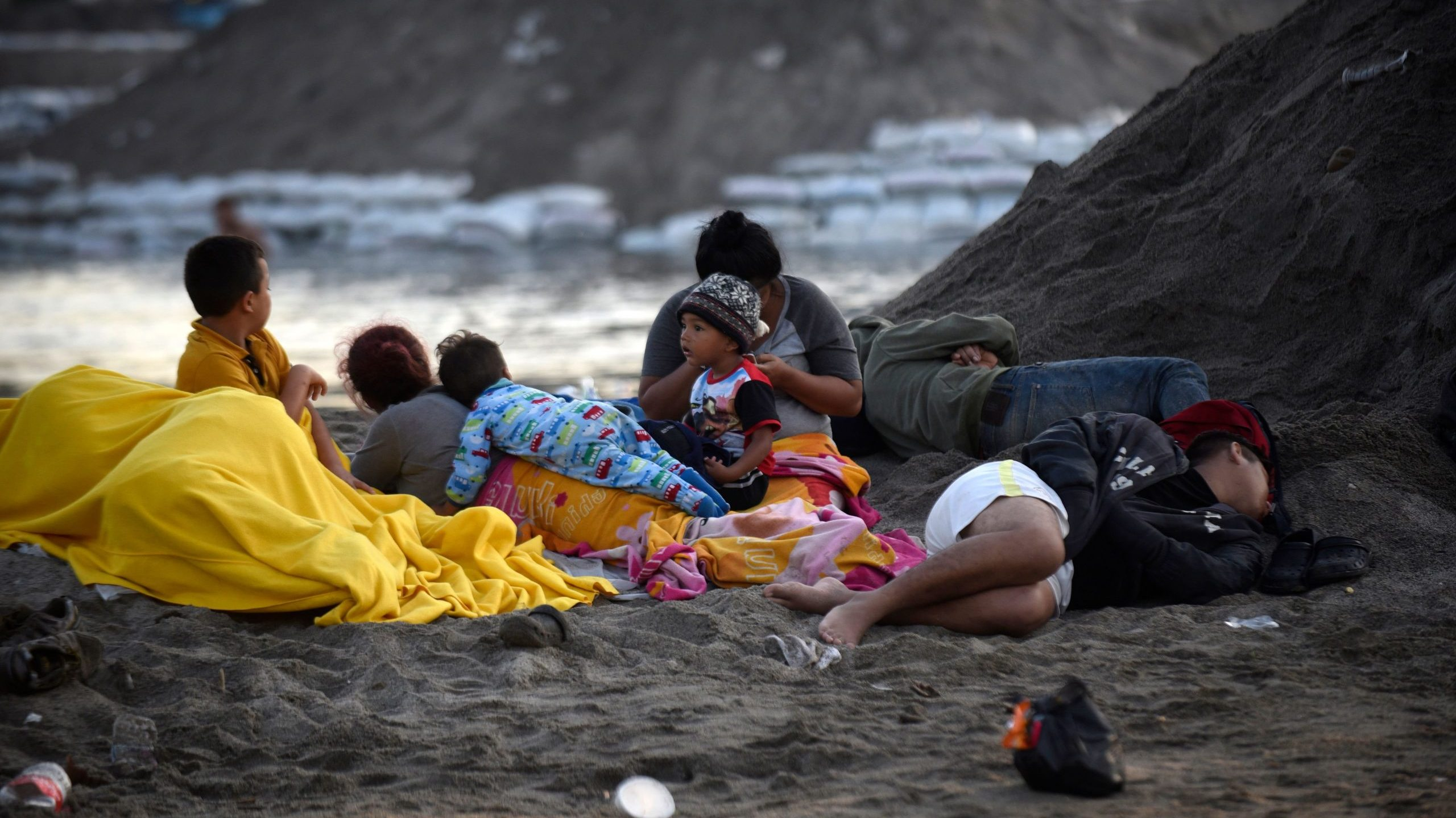 Central American migrants, heading in a caravan for the U.S., wake up on the bank of the Suchiate River, where they spent the night, in Ciudad Hidalgo, Mexico, after crossing from Tecun Uman, Guatemala, on Jan. 21, 2020. (Credit: Johan Ordonez / AFP / Getty Images)