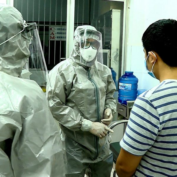 Medical personnel wearing protectice suits interact with two patients (R on bed and standing) tested positive to the coronavirus in an isolation room at Cho Ray hospital in Ho Chi Minh City on January 23, 2020. (Credit: STR/Vietnam News Agency/AFP via Getty Images)