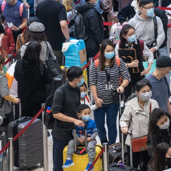 Travelers wearing face masks wait in line at the departure hall of West Kowloon Station on Jan. 23, 2020 in Hong Kong. (Credit: Anthony Kwan/Getty Images)