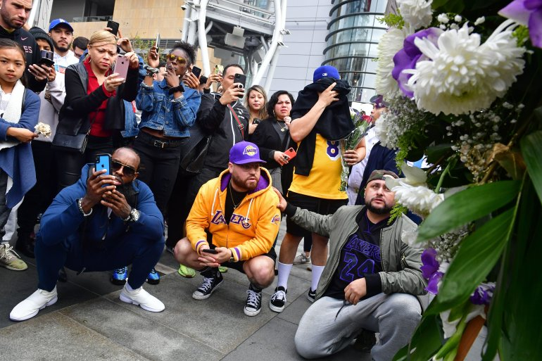 People gather around a makeshift memorial for former NBA star Kobe Bryant in front of Staples Center in Los Angeles on Jan. 26, 2020. (Photo by Frederic J. Brown/AFP via Getty Images)