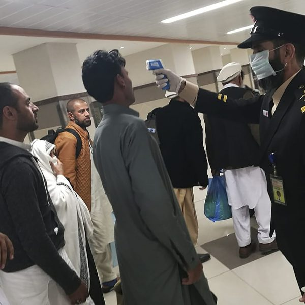An airport official checks the temperature of a passenger upon his arrival at the Bacha Khan International Airport in Peshawar on January 27, 2020.