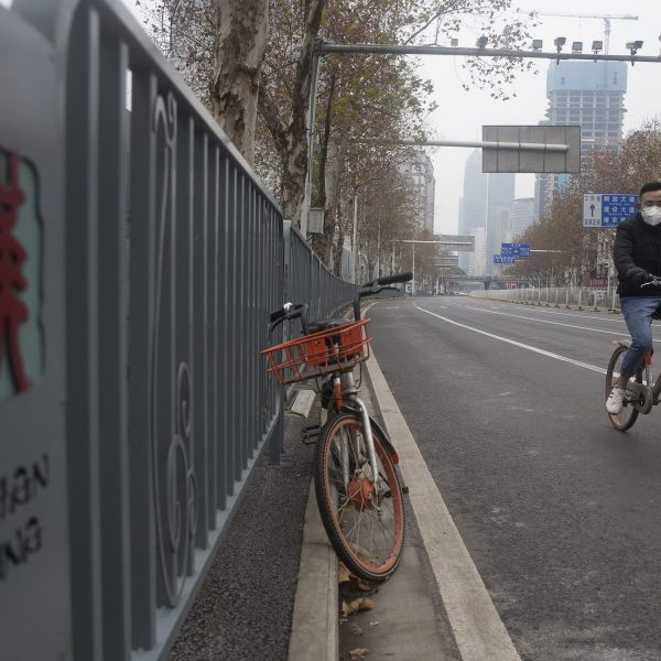 A man wearing a protective mask rides a motorized bike on an empty road on Jan. 27, 2020, in Wuhan, China. (Credit: Getty Images)
