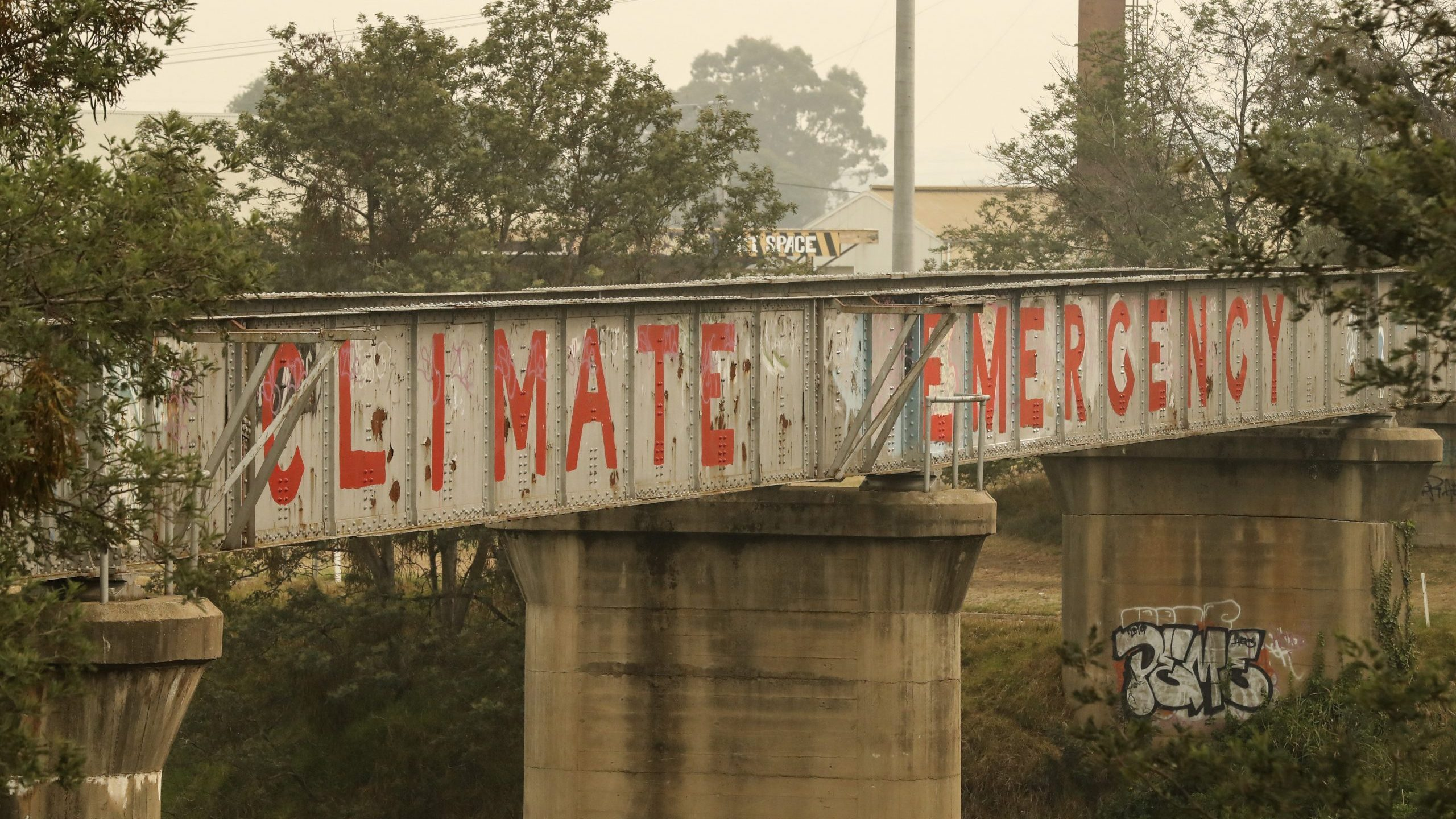 Graffiti is seen on a bridge on Jan. 3, 2020, in Bairnsdale, Australia, as wildfire evacuations begin for thousands of stranded people nearby. (Credit: Darrian Traynor/Getty Images)