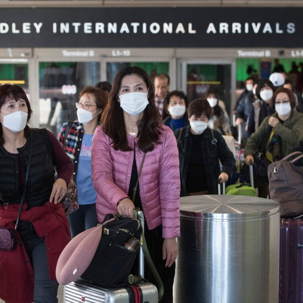 Passengers wear protective masks to protect against the spread of the Coronavirus as they arrive on a flight at Los Angeles International Airport in Los Angeles on Jan. 29, 2020. (Credit: MARK RALSTON/AFP via Getty Images)