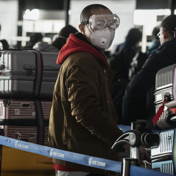 A man wears a protective mask and goggles as he lines up to check in to a flight at Beijing Capital Airport on Jan. 30, 2020, in Beijing, China. The number of cases of a deadly new coronavirus rose to over 7,000 in mainland China by then. (Credit: Kevin Frayer/Getty Images)