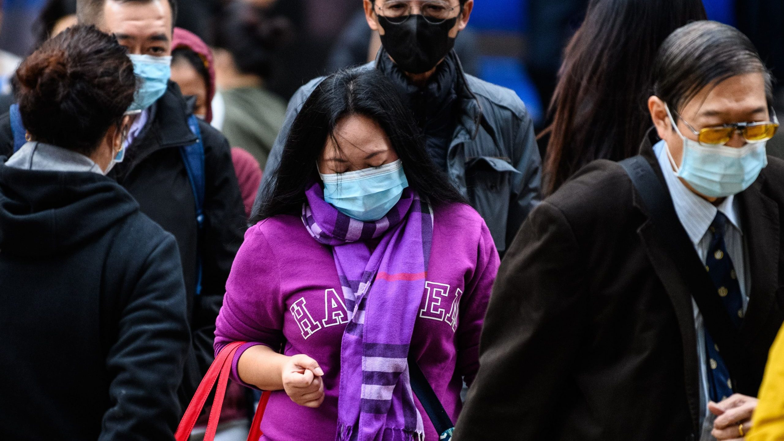 Pedestrians wearing face masks as a preventative measure following a virus outbreak which began in the Chinese city of Wuhan, cross a road in Hong Kong on Jan. 31, 2020. (Credit: ANTHONY WALLACE/AFP via Getty Images)