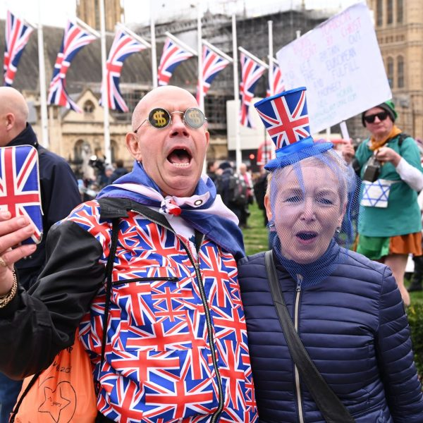 Brexit supporters wearing Union Flag-themed dress react in Parliament Square in London on Jan. 31, 2020, the day the U.K. formally leaves the European Union. (Credit: GLYN KIRK/AFP via Getty Images)
