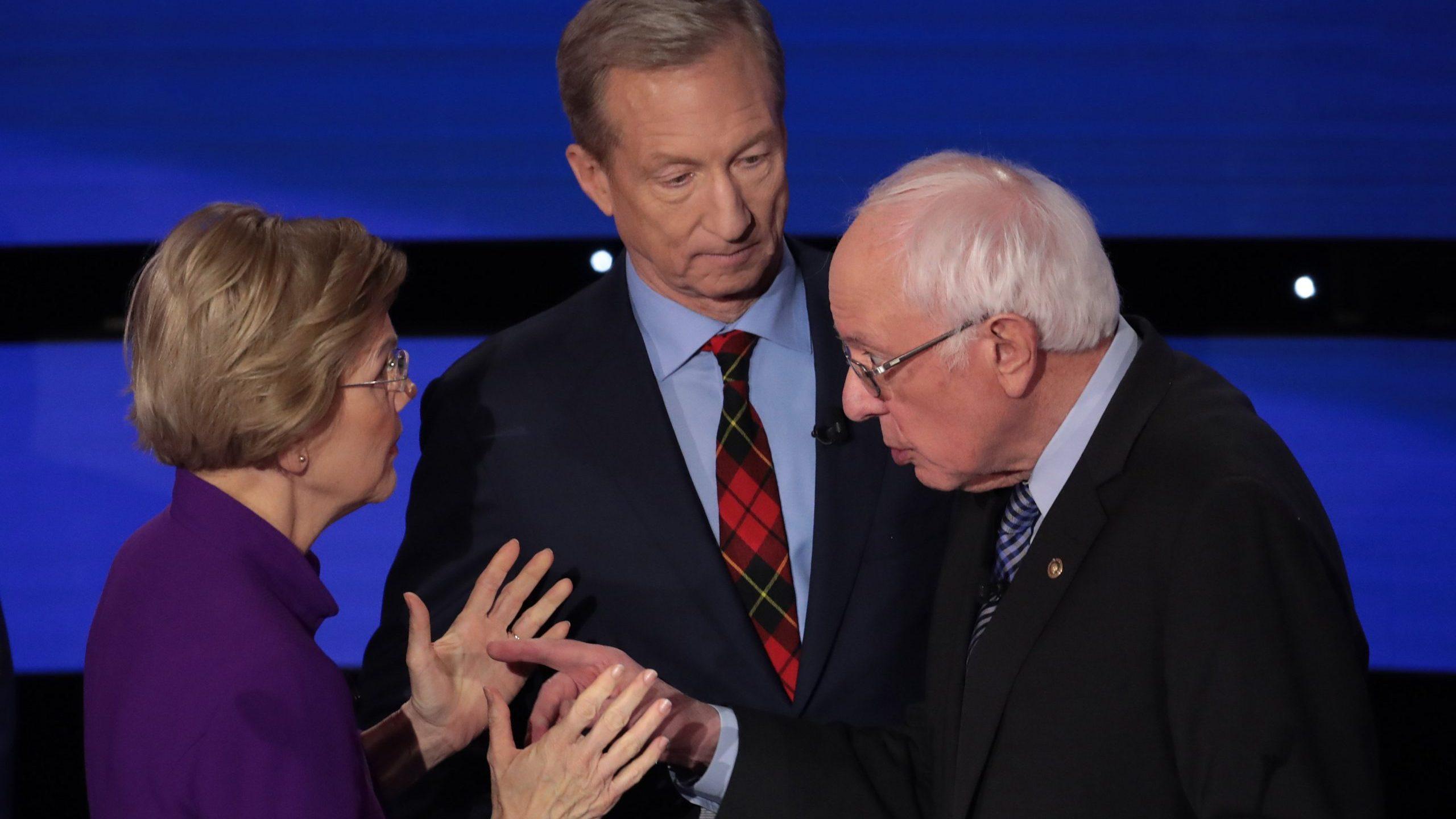 Sen. Elizabeth Warren (D-MA) and Sen. Bernie Sanders (I-VT) speak as Tom Steyer looks on after the Democratic presidential primary debate on Jan. 14, 2020 in Des Moines, Iowa. (Credit: Scott Olson/Getty Images)