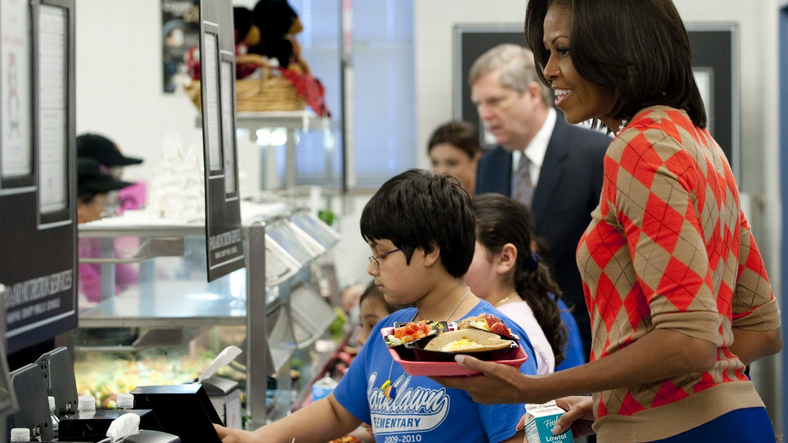 Michelle Obama holds a plate of food while walking down the school lunch line in the cafeteria at Parklawn Elementary School in Alexandria, Virginia, on Jan. 25, 2012. (Credit: SAUL LOEB/AFP via Getty Images)