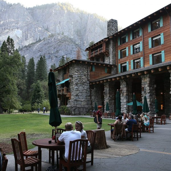 Park visitors sit outside the Ahwahnee Hotel in Yosemite National Park on Aug. 28, 2013. (Credit: Justin Sullivan / Getty Images)