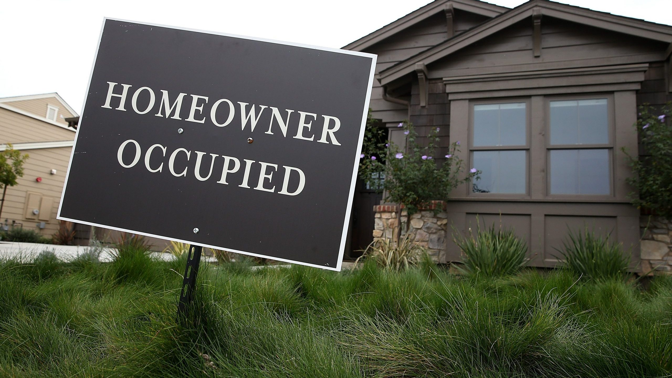 A homeowner occupied sign is posted in front of a recently purchased new home at the Rose Lane housing development in Lakespur on Jan. 27, 2015. (Credit: Justin Sullivan / Getty Images)