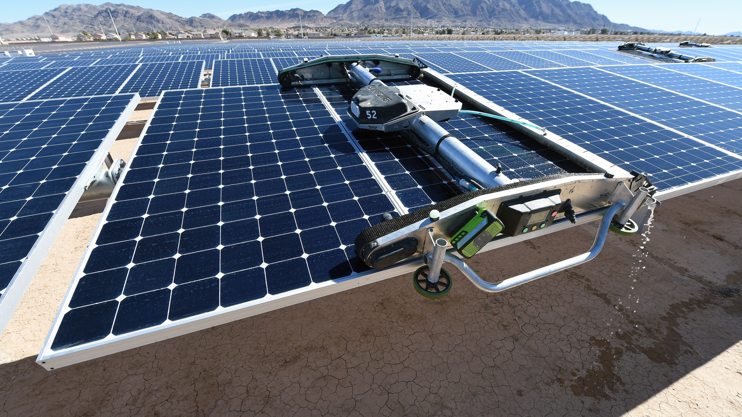A panel-washing robot cleans a row of solar panels during a dedication ceremony to commemorate the completion of the 102-acre, 15-megawatt Solar Array II Generating Station at Nellis Air Force Base on Feb. 16, 2016, in Las Vegas, Nevada. (Credit: Ethan Miller/Getty Images)