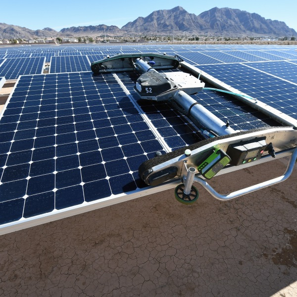 A panel-washing robot cleans a row of solar panels during a dedication ceremony to commemorate the completion of the 102-acre, 15-megawatt Solar Array II Generating Station at Nellis Air Force Base on Feb. 16, 2016, in Las Vegas, Nevada. (Ethan Miller/Getty Images)