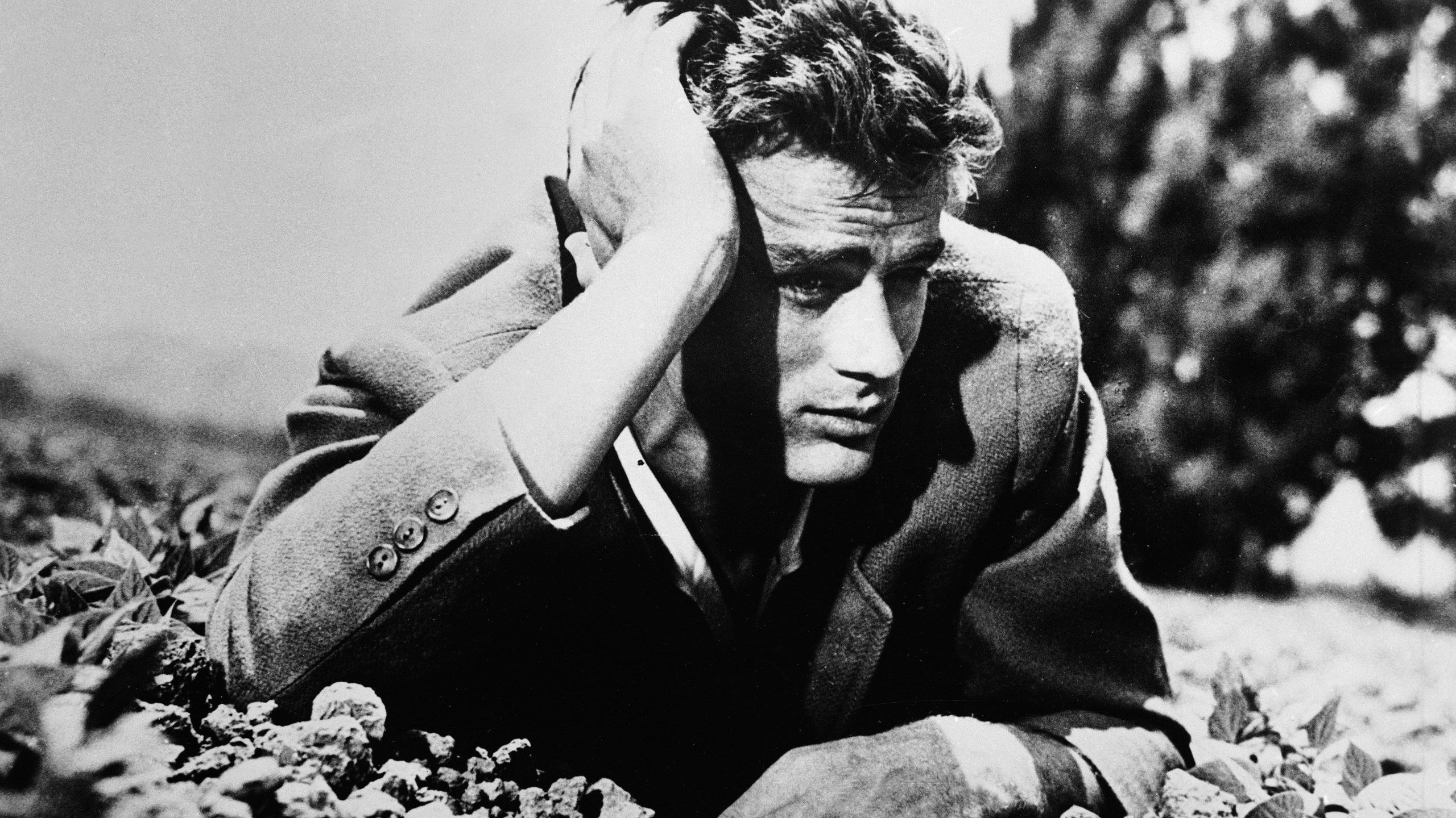 American actor James Dean lies in the dirt with his head leaning on his hand in this 1950s photo. (Credit: Hulton Archive/Getty Images)