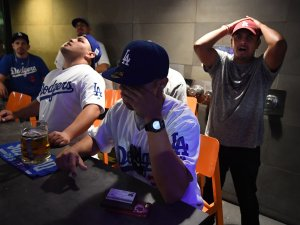 Dodgers fans react on Nov. 1, 2017 at a bar in downtown Los Angeles after watching their team lose 5-1 to the Houston Astros in the final game of the World Series. (Credit: MARK RALSTON/AFP via Getty Images)