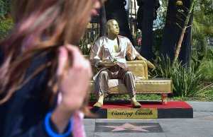 A woman walks past a gold sculpture of Harvey Weinstein on his infamous casting couch holding an Oscar statue beside Elvis Presley's Hollywood Walk of Fame Star on March 1, 2018. (Credit: Frederic J. Brown / AFP / Getty Images)