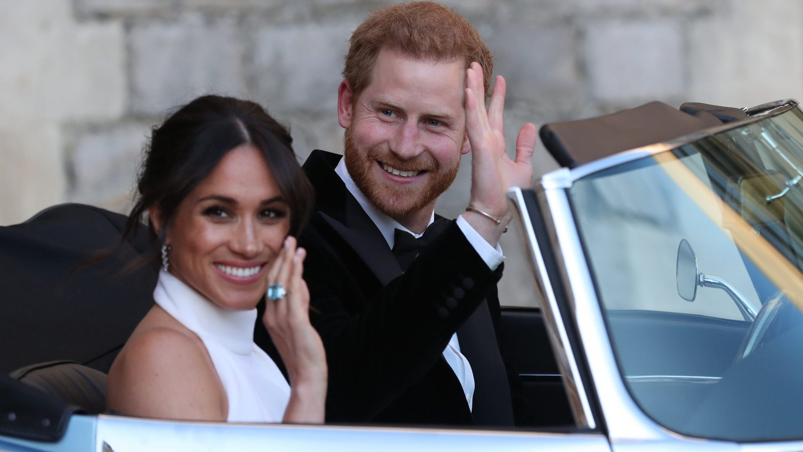 Duchess of Sussex and Prince Harry, Duke of Sussex wave as they leave Windsor Castle after their wedding to attend an evening reception at Frogmore House, hosted by the Prince of Wales on May 19, 2018 in Windsor, England. (Credit: Steve Parsons - WPA Pool/Getty Images)