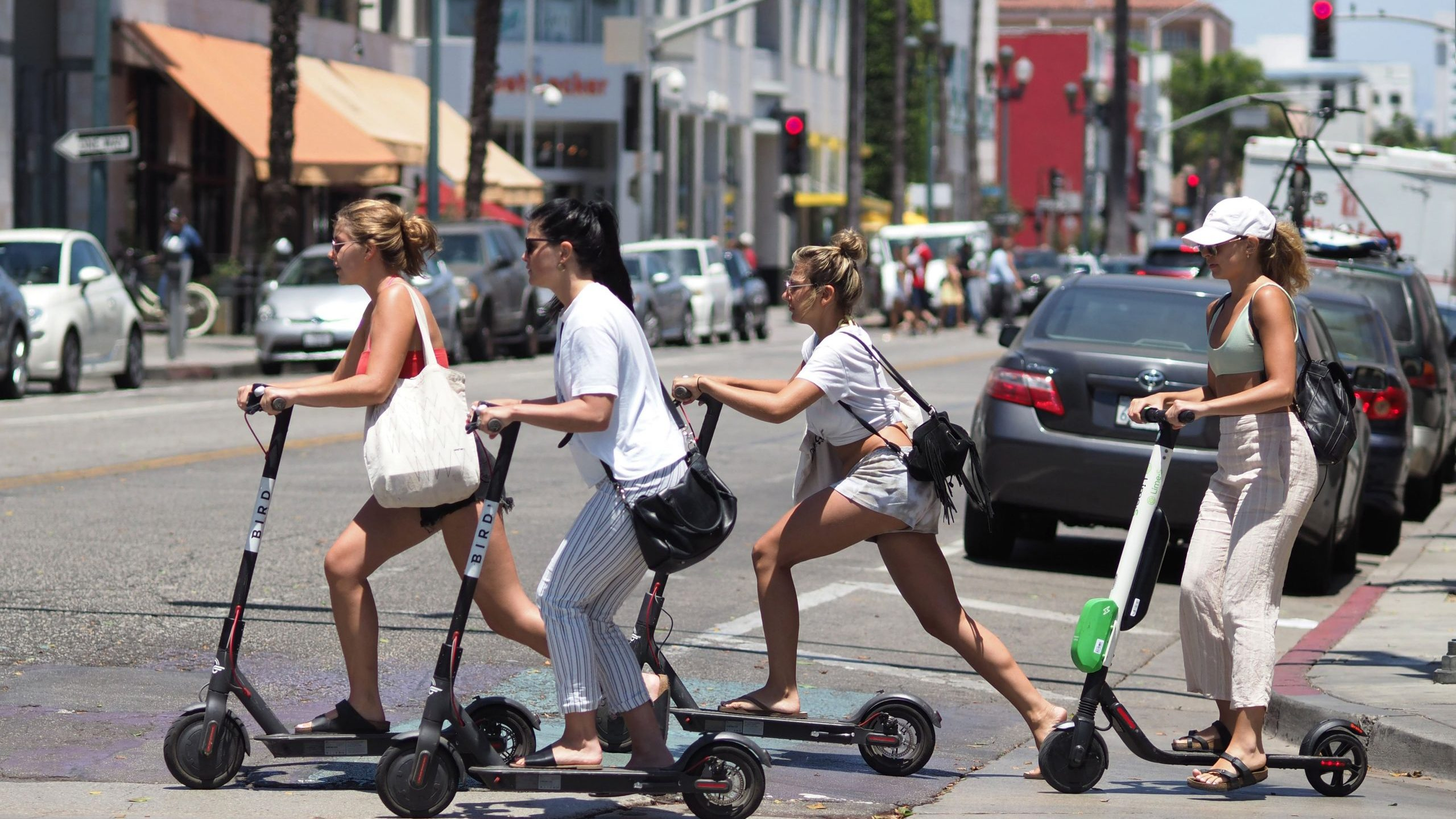 Young women ride electric scooters in Santa Monica on July 13, 2018. (Credit: Robyn Beck/AFP via Getty Images)