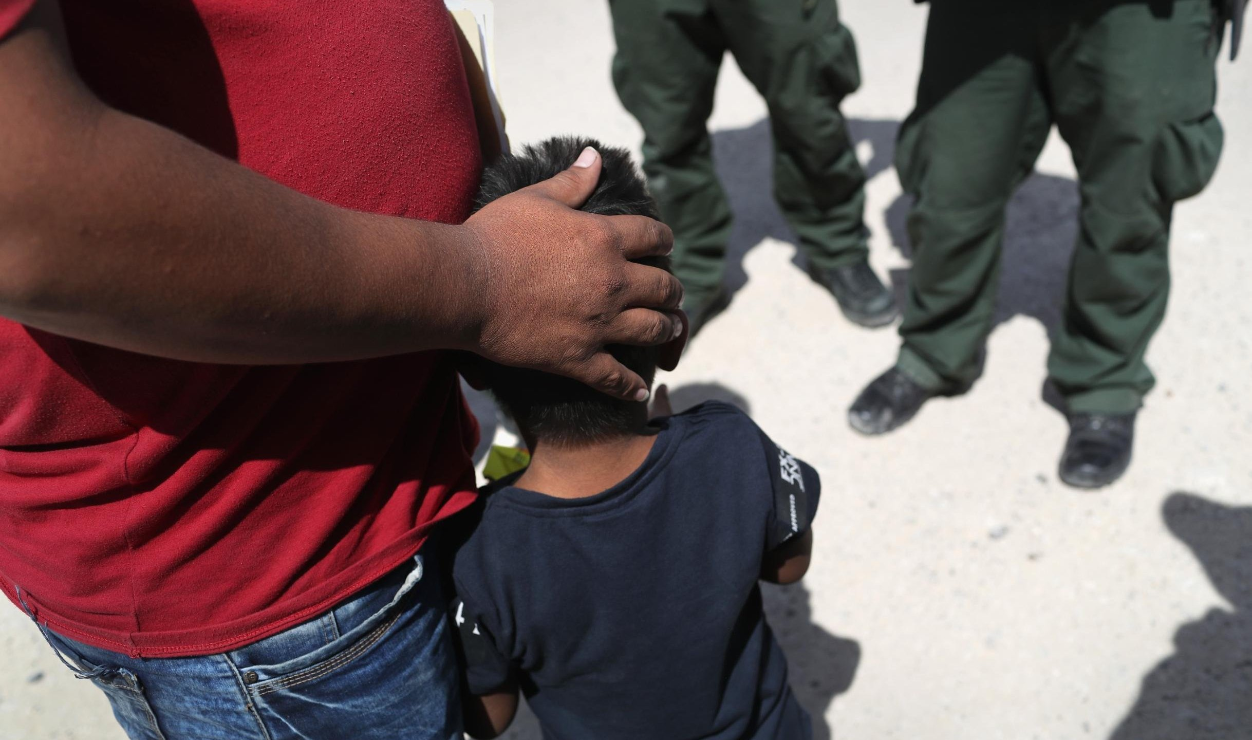 U.S. Border Patrol agents take a father and son from Honduras into custody near the U.S.-Mexico border on June 12, 2018 near Mission, Texas.(Credit: John Moore/Getty Images)