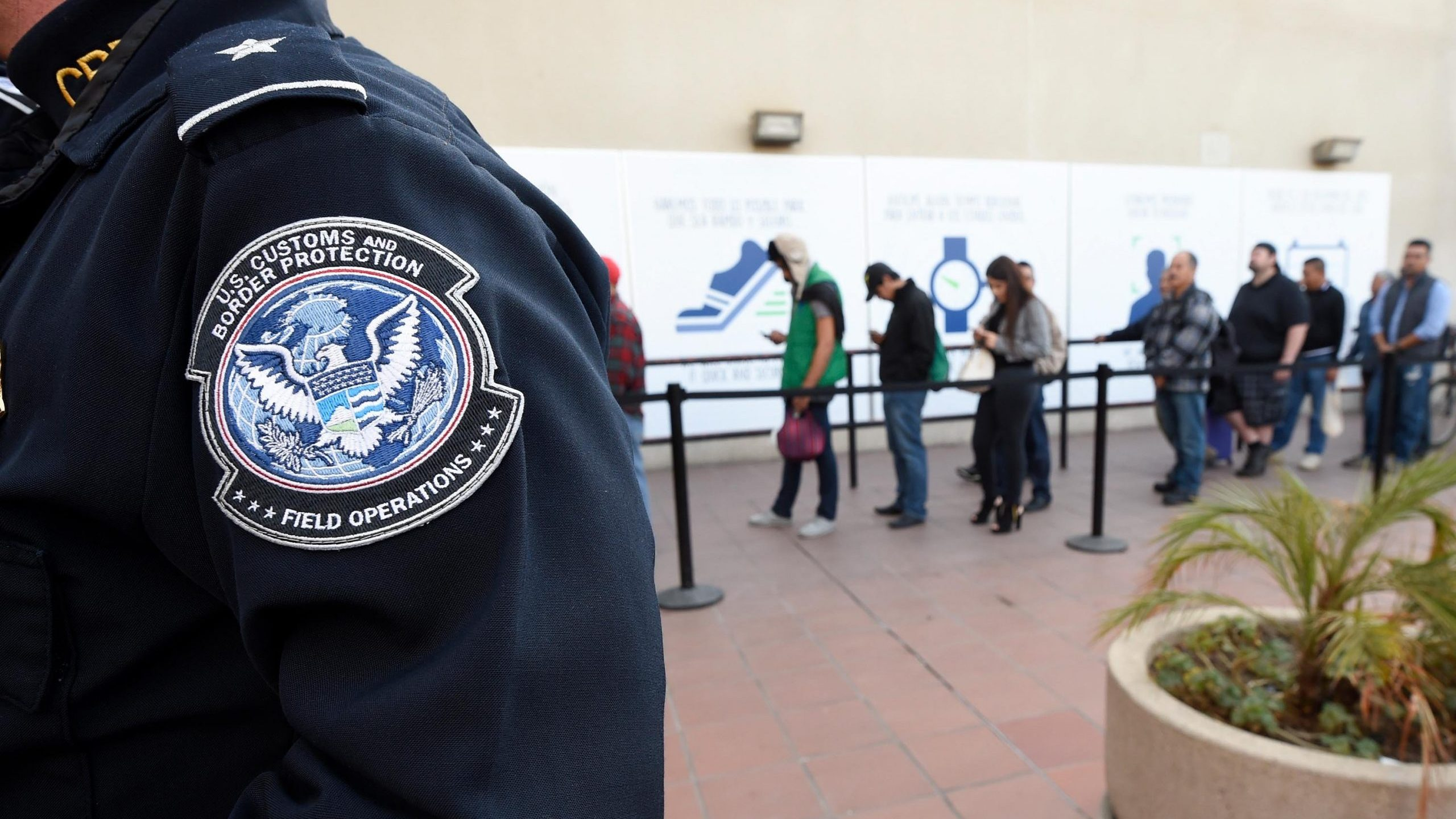 In this Dec. 10, 2015, file photo, pedestrians crossing from Mexico into the United States at the Otay Mesa Port of Entry wait in line in San Diego. (Denis Poroy/Associated Press)