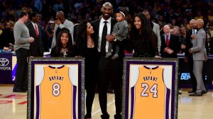 Kobe Bryant poses with his family at halftime after both his #8 and #24 Los Angeles Lakers jerseys are retired at Staples Center on Dec. 18, 2017, in Los Angeles. (Credit: Harry How/Getty Images)