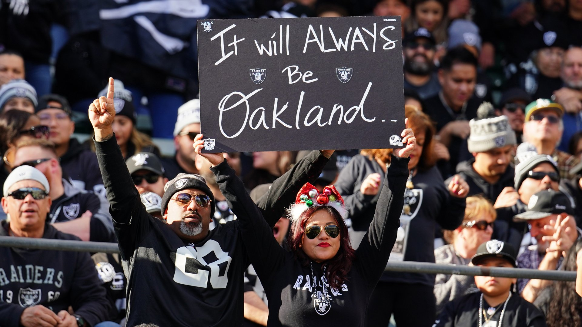 Fans in the stands hold signs during a game between the Oakland Raiders and the Jacksonville Jaguars in Oakland on Dec. 15, 2019. (Credit: Daniel Shirey / Getty Images)