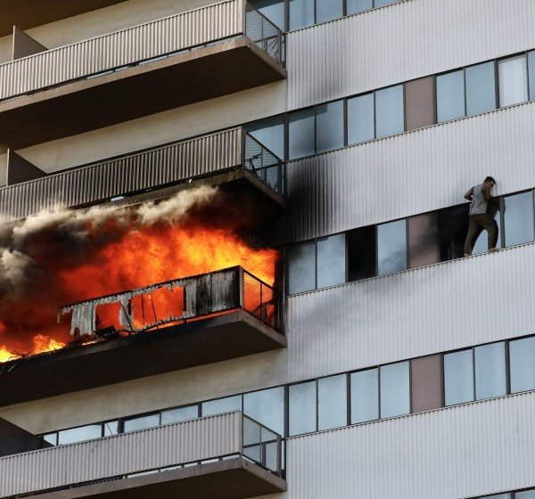 A man is seen clinging to the window of a Brentwood-area high-rise during a fire on Jan. 29, 2020. (Credit: Al Seib / Los Angeles Times)