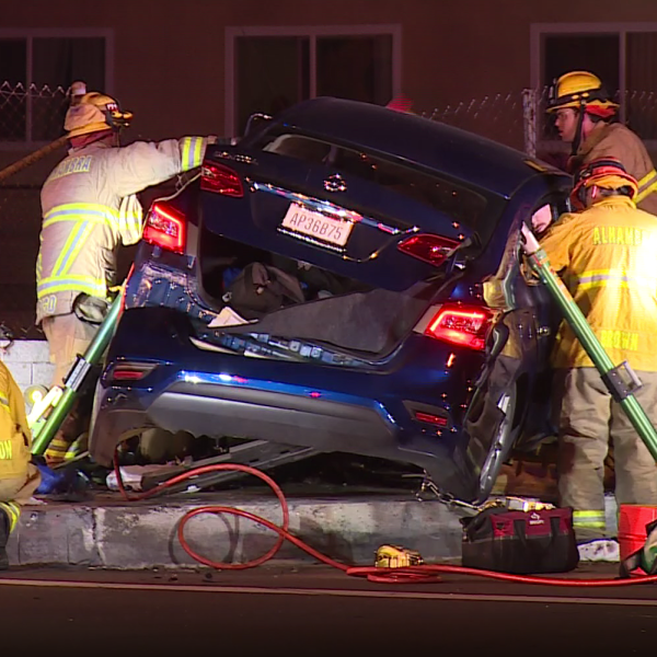 Firefighters rescue a trapped passenger from a car that officials say accelerated towards officers then crashed following a pursuit in Alhambra on Jan. 5, 2019. (Credit: RMG News)