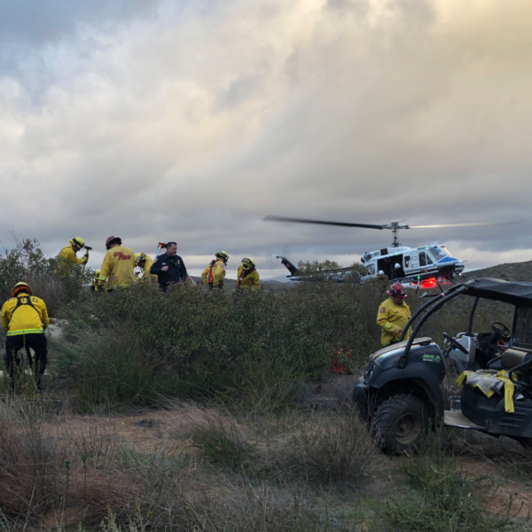 A rescue crew works to hoist a man aboard a helicopter after a climbing accident on a cliff overlooking San Pasqual Valley in San Diego. (Credit: Cal Fire)