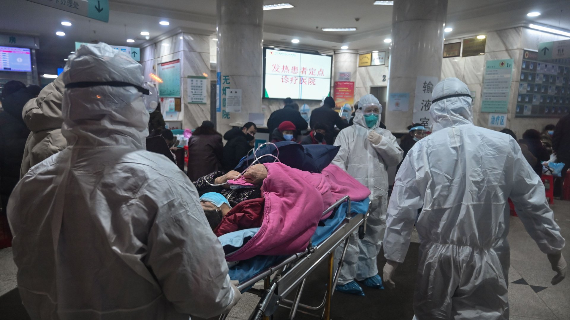 In this photo taken on January 25, 2020, medical staff wearing protective clothing to protect against a previously unknown coronavirus arrive with a patient at the Wuhan Red Cross Hospital in Wuhan. (Credit: Hector Retamal/AFP/Getty Images)