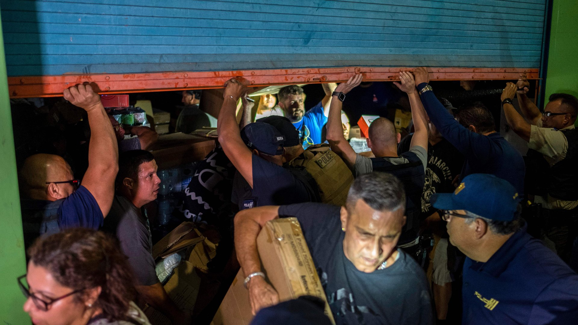 Police arrive as people break into a warehouse filled with supplies, believed to have been from when Hurricane Maria struck the island in 2017 in Ponce, Puerto Rico on January 18, 2020, after a powerful earthquake hit the island. (Credit: Ricardo Arduengo/AFP'Getty Images)