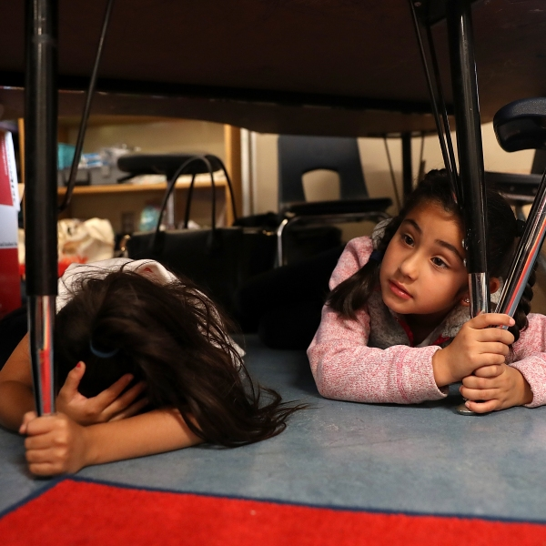 Students take cover under their desks during a school drill on Oct. 18, 2018, in San Francisco, California. (Credit: Justin Sullivan/Getty Images)