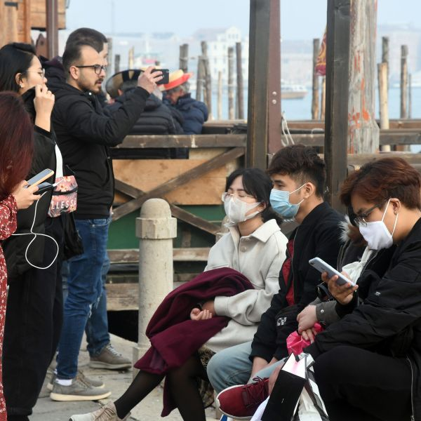 Tourists wearing protective masks visit Venice on Feb. 25, 2020, during the usual period of Carnival festivities which were cancelled due to a coronavirus outbreak in northern Italy. (Credit: Andrea Pattaro / AFP / Getty Images)